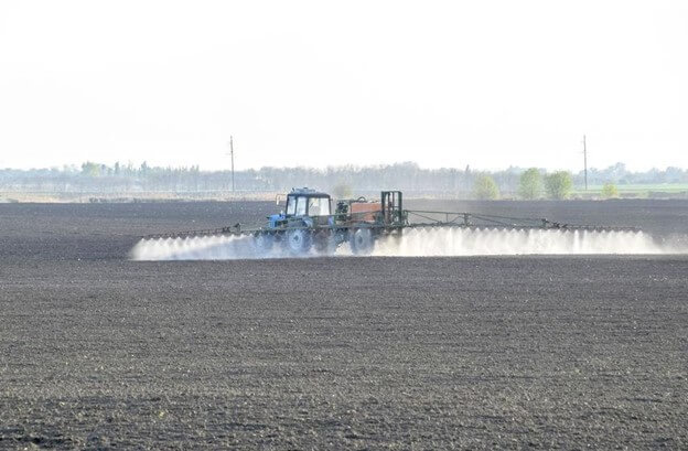 Farmer tending their crops with agrochemicals like pesticides, herbicides and fertilizer.