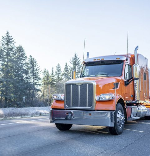Orange big rig American bonnet long haul semi truck with long cylindrical tank semi trailer transporting liquid and liquefied chemical cargo on the winter frosty road