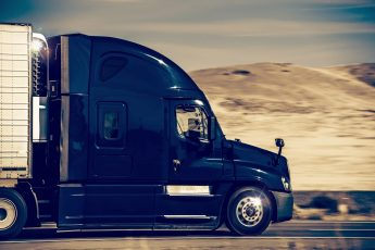 Speeding Dark Blue Semi Truck in Nevada, United States. Trucking in Western USA.